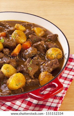 Stew with Carrots and Potatoes - a simple stew in a red pot, with carrots and potatoes. - stock photo