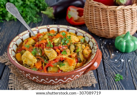 Stew with chicken and vegetables. Chicken with eggplant, bell peppers, carrots and tomatoes