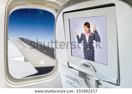 Stewardess informed of the display on the aircraft seat. Monitor and a window on the plane. Air hostess on television in flying aircraft. The screen with flight crew next window with aircraft's wing.