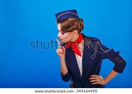 Stewardess with face art asks for silence. Young attractive girl in a blue suit flight attendants. Air freight. Service. - stock photo