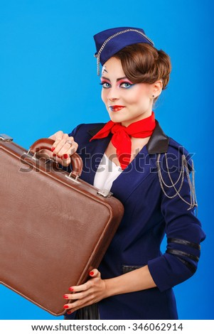 Stewardess with face art holds suitcase. Young attractive girl in a blue suit flight attendants. Airfreight. Service. Baggage. - stock photo