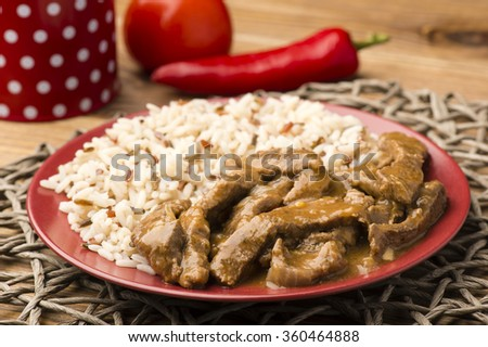 Stewed beef and rice on the red plate on wooden background. - stock photo