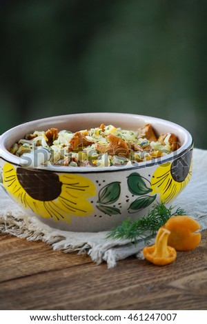 Stewed cabbage and chanterelles on the old wooden background in rustic style