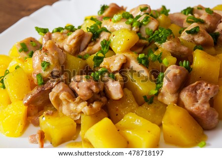 stewed chicken meat with potatoes in a plate on wooden table