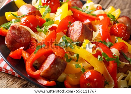 Stewed pepper with sausages and tomatoes close-up on a plate on a table. horizontal
