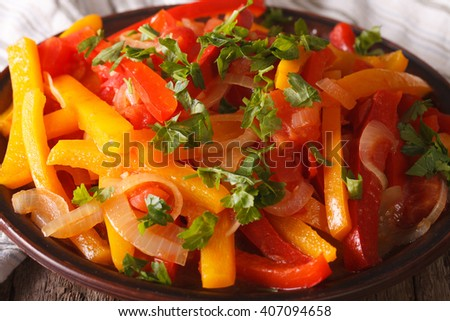 Stewed peppers with tomatoes and onions close up on a plate. horizontal