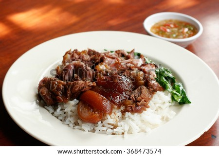 Stewed pork leg on rice with spicy sour sauce. - stock photo