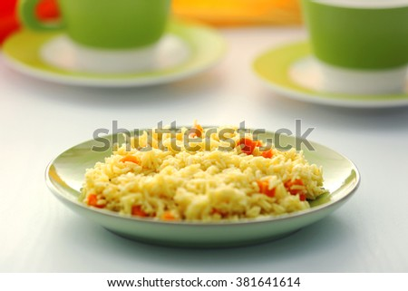 Stewed rice with a carrot on a plate