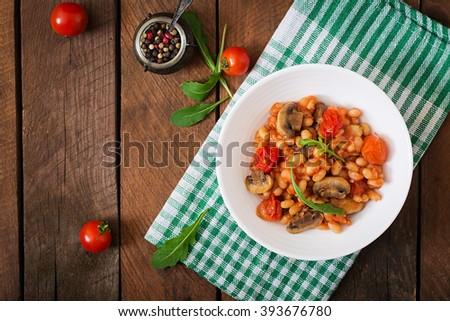 Stewed white beans with mushrooms and tomatoes with spicy sauce in a white bowl. Top view - stock photo