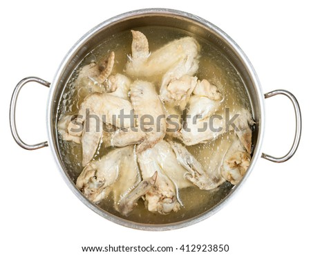 stewpan with boiled chicken wings in greasy chicken bouillon isolated on white background