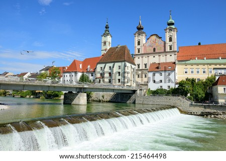 STEYR, AUSTRIA - AUGUST 09, 2014: Mouth of the Steyr on the Enns River in Upper Austria. At the foreground the St.Michaels Church with gable Fresco. Steyr is the 3rd largest town in Upper Austria - stock photo