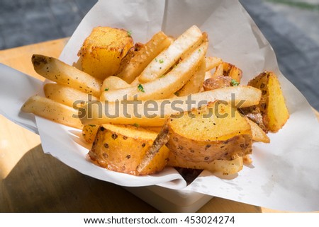 Stick and wedge French fries on white bowl with white paper sheet - close up - stock photo