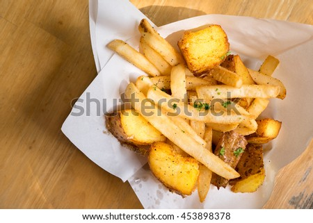 Stick and wedge French fries on white bowl with white paper sheet - top view - stock photo