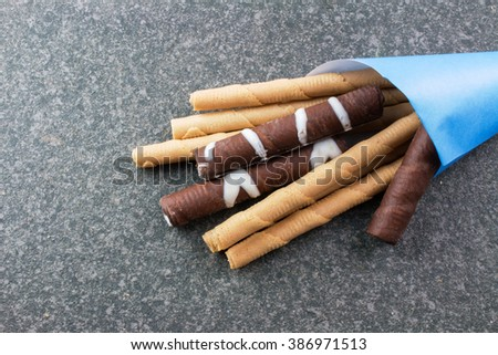 Stick Cookies with Blue Paper Cone on Rustic Table.