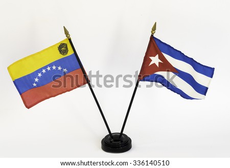 Stick flags of Venezuela and Cuba on a stand against white background - stock photo
