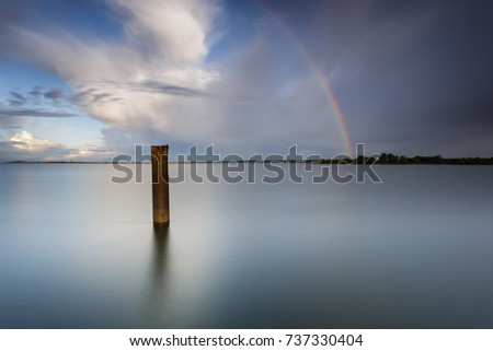 Stick in the water under the rainbow