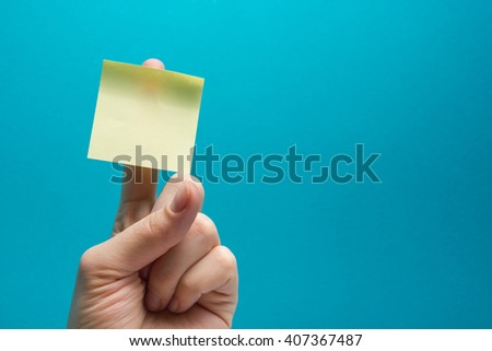 Stickers on the fingers of the hand on blue background. Free copy space for your ad. Hand with yellow sticky note
