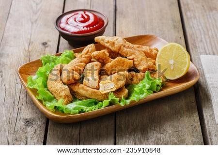 sticks breaded chicken with lemon - stock photo