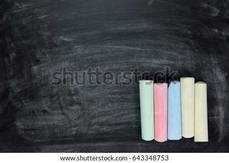 Sticks of colored chalk arranged in a neat row in the corner on a chalkboard with copy space and texture