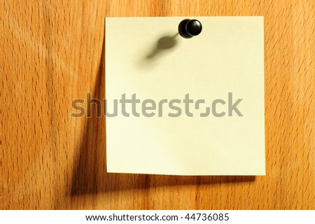 Sticky note and push pin on wooden board
