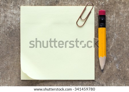 Sticky note paper with paperclip and pencil - stock photo