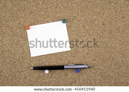 Sticky note with pen on cork board - stock photo