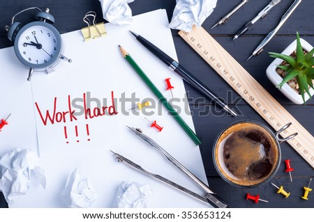 Sticky note with the word Work hard. White blank paper, crumpled paper, clock,  pen, pencil, ruler, divider compass and cup of coffee on a dark wooden background. Office workplace. - stock photo