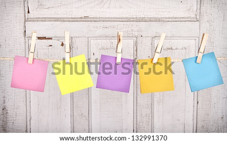 Sticky notes on a clothes line with an antique cracked wooden panel for the background - stock photo