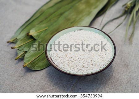 sticky rice, reed leaf, two materials for Zongzi, a Chinese Traditional Food for celebrate Dragon Boat Festival. - stock photo