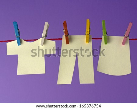 Sticky yellow papers notes hanging on clothes peg, on a purple background.