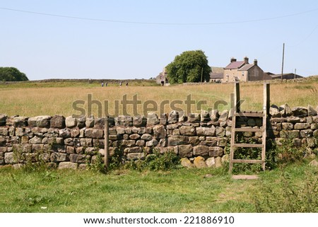 Stile over a dry stone wall on a farm in Northumberland, England. The isolated farmhouse is in the distance across a meadow. - stock photo