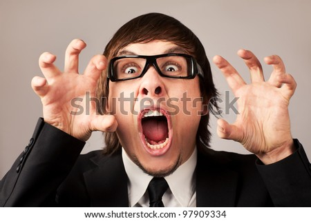 Stilish businessman screaming ang expressing anger. On a grey background - stock photo