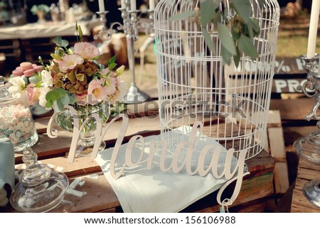 Still glass vases and a white bird cage and the inscription Monday - stock photo