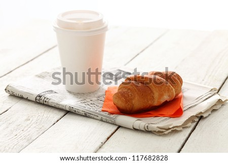 Still hot coffee with fresh tasty croissant on newspaper over wooden surface - stock photo