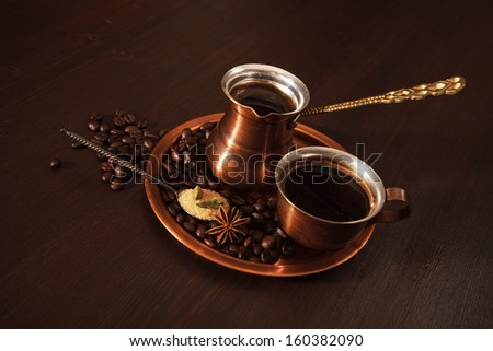 Still life, a copper coffee set consisting of a plate, a cezve, which is a turkish coffee pot, and a cup. - stock photo