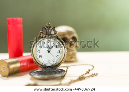 Still life antique clock placed on a wooden floor and a red shotgun shell with human skull on the back.