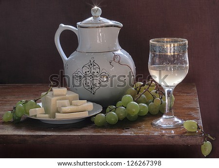 Still-life, appetizing house cheese with juicy grapes and a fragrant drink - stock photo