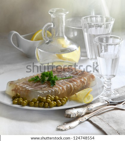 Still-life, appetizing jellied meat with green peas and the misted over wine-glass of cold vodka