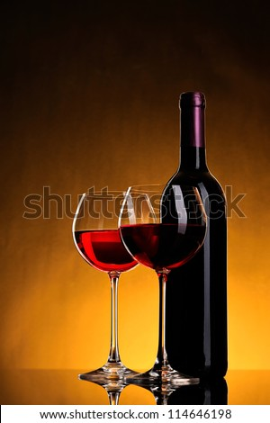 still-life arrangement: bottle of wine and two glasses wine on yellow background - stock photo