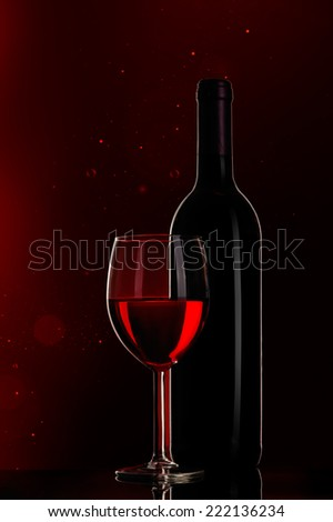 still-life arrangement: bottle of wine and wine glass on red background - stock photo
