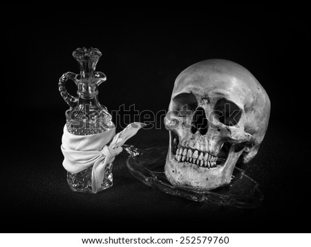 Still life art on skull with crystal glassware light painting technique black and white version - stock photo