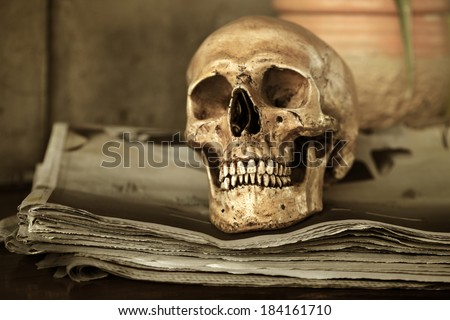 Still life art photography concept on human skull on old newspaper bun