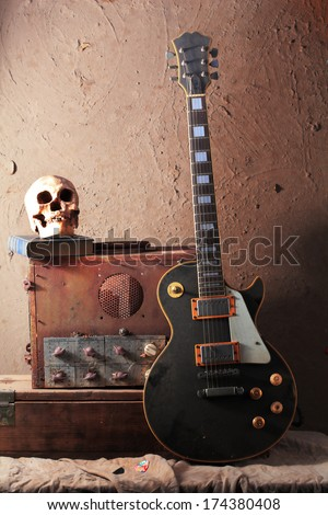 Still life art photography of vintage electric guitar and rare vintage amplifier on grunge background with skull skeleton - stock photo