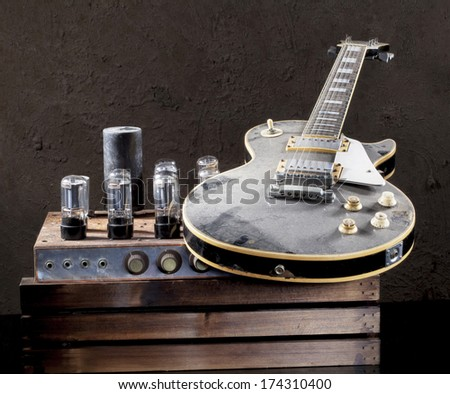 Still life art photography of vintage electric guitar cover with dust and rare vintage valve amplifier on grunge background  - stock photo