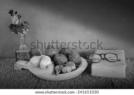 Still life art photography on fruits set with old book glasses and dry roses in vase over grunge backdrop and artificial grass floor black and white version - stock photo
