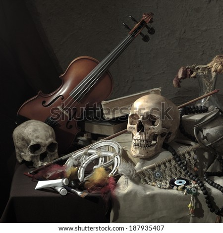 Still life art photography on skulls and violin on table with fabric