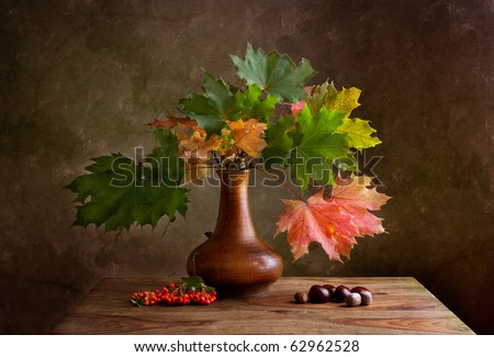 Still Life Autumn concept image with chestnuts and maple leafs