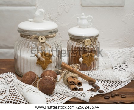 still life, banks for loose products with cupcakes and cinnamon on a background of lace - stock photo