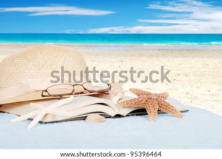 Still life beach concept with book glasses and hat - stock photo