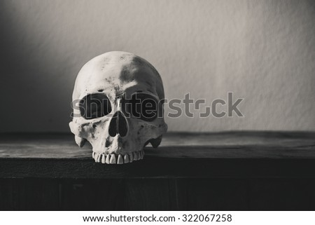 Still life black and white photography with human skull on wooden table - stock photo
